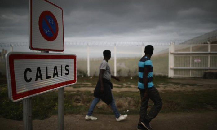 Migrants in Calais erect flaming barricade built of branches