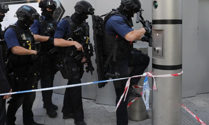 Armed police are seen searching London Bridge after last night's events