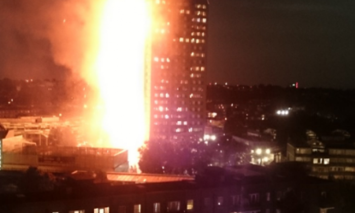 Authorities continue to battle flames on Grenfell Tower as witnesses report people remain trapped