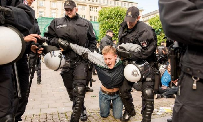 A protester is led away by police ahead of the G20 summit