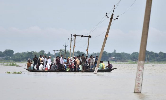Indian villagers travel by boat through floodwaters