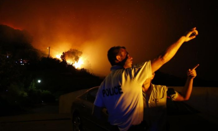 Police were on hand in Biguglia, Corsica as the fire raged on