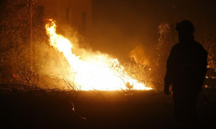 A firefighter looks on whilst working to put out fire in Biguglia, Corsica