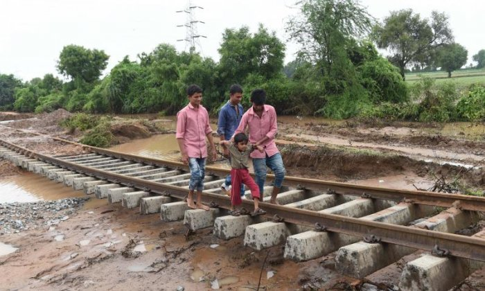 Villagers travel along damaged railway tracks in the Godha village