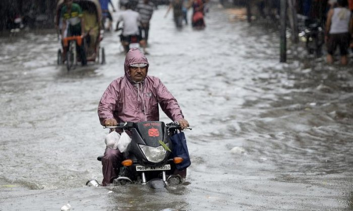 A man continues to ride his bike despite the water