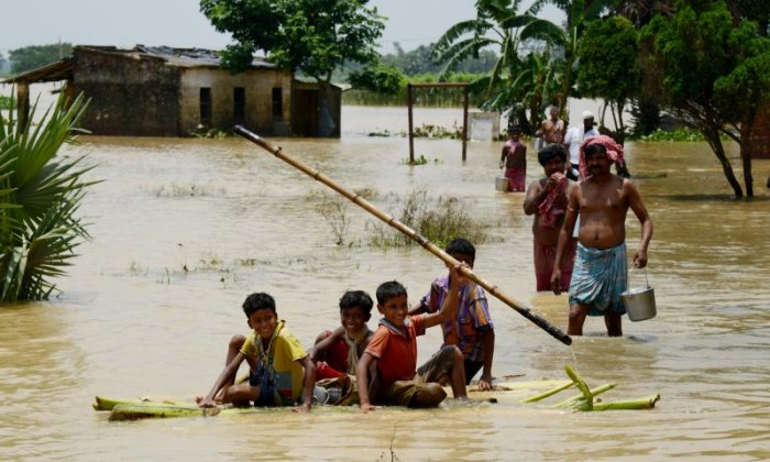 Children in Udaynarayanpur travel on a makeshift raft