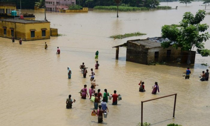 Residents try to get through floodwater to access relief materials