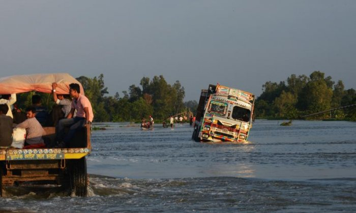 Vans struggle to get through the water in the Malda district of West Bengal, India