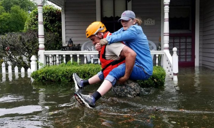 A resident is carried away from her home by a Texas National Guardsman