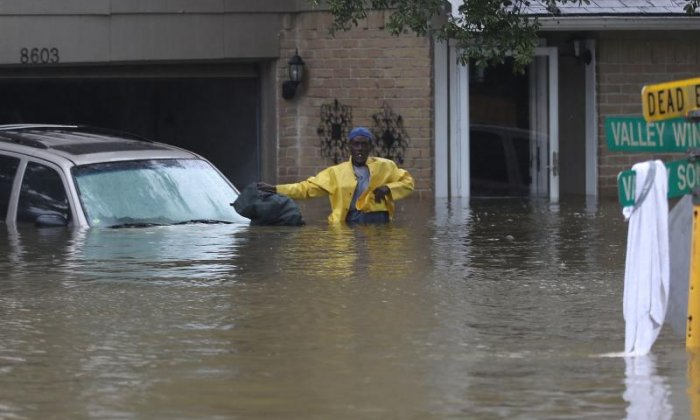 Floodwaters are seen above waist height at people's homes