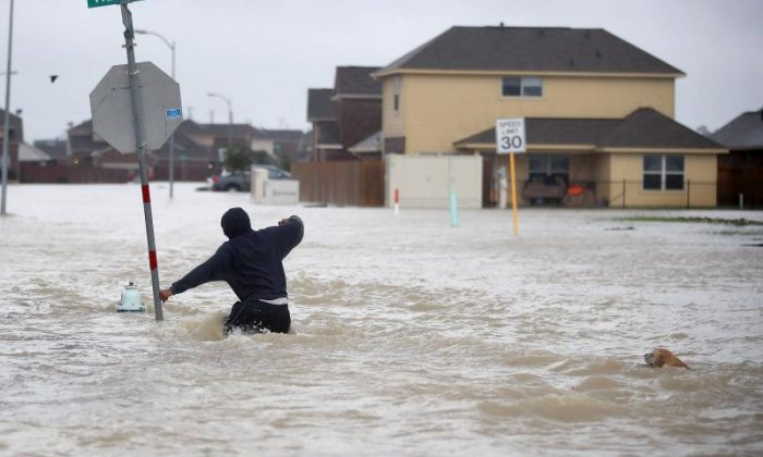 Someone struggles as they walk up a flooded street