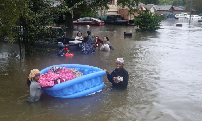 People move through the floodwaters with their belongings