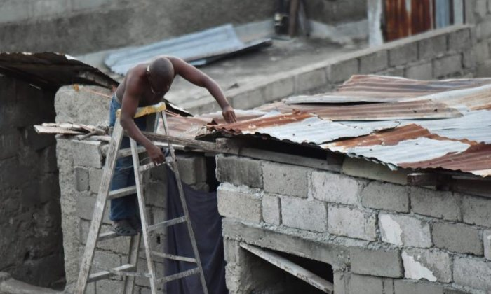 A man in Haiti is seen repairing his roof in preparation