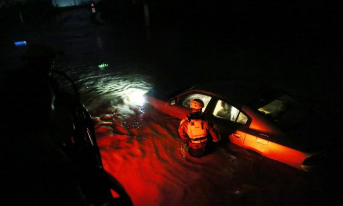 Rescue workers are seen wading through the floodwater