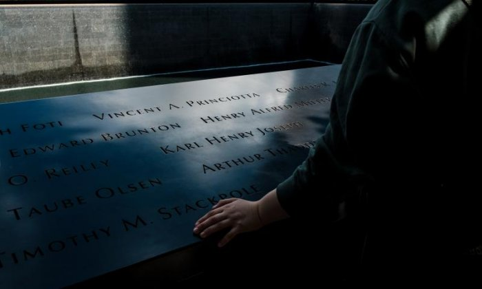 An individual looks at the names of the victims inscribed on the monument