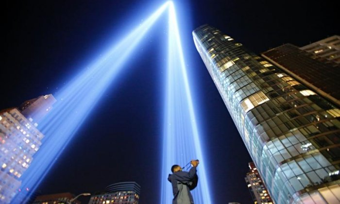 A man takes a picture of the Tribute in Light