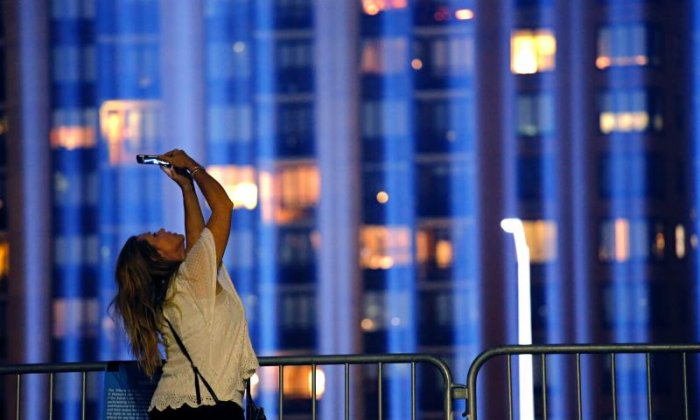 A woman takes a picture of the Tribute in Light