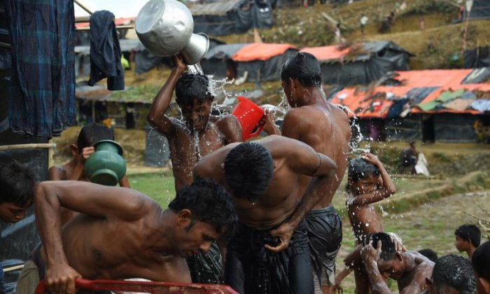 Rohingya refugees wash with pots of water