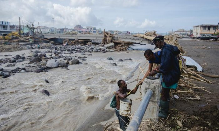 A man is helped up after collecting water from a river