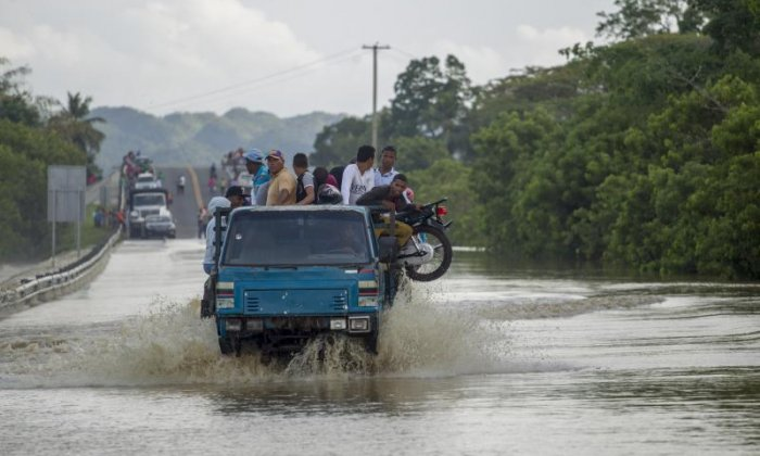 Locals travel through floodwaters left by Hurricane Maria