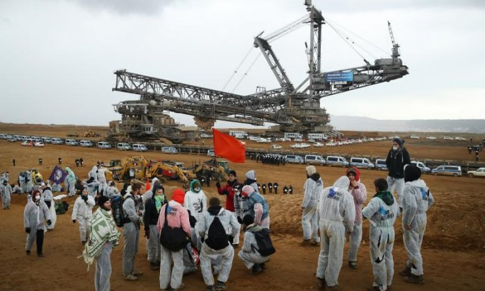 Climate activists look over at a bucket excavator