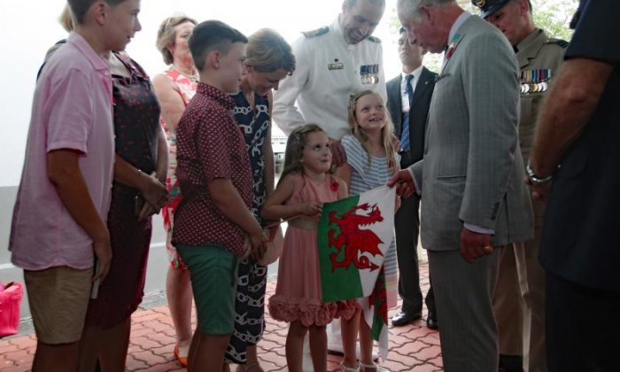A girl shows Prince Charles a Welsh flag in Penang, Malaysia