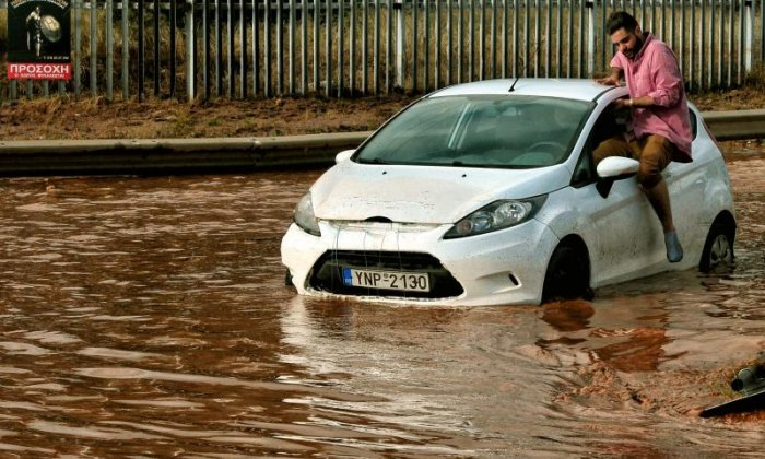 A man attempts to get in a car about to be stuck in floodwater