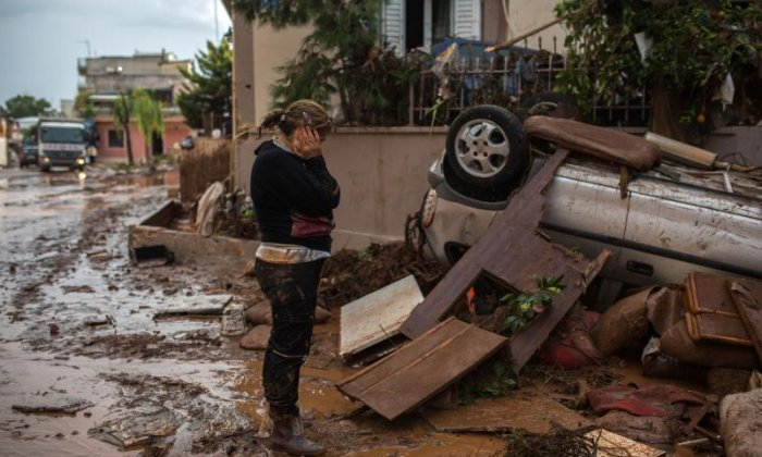 A woman looks in despair at flood damage