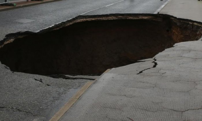 Woman swallowed up by ground as huge sinkhole appears in street