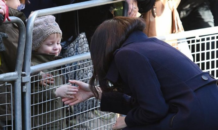Meghan Markle greets a young member of the crowd