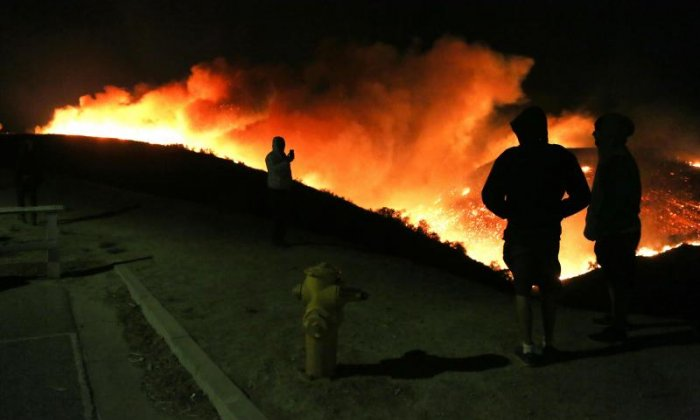 People look on at the fire burning