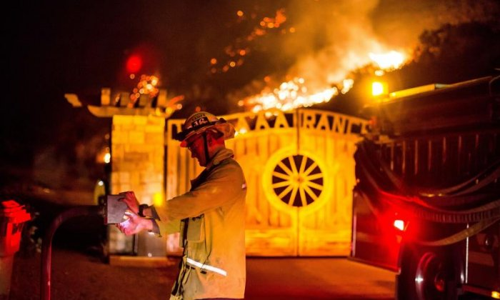 A firefighter is seen opening a gate