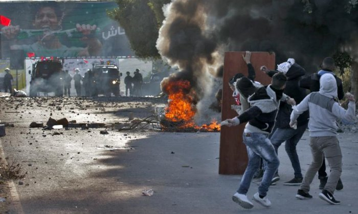 Palestinians throw stones towards Israeli forces