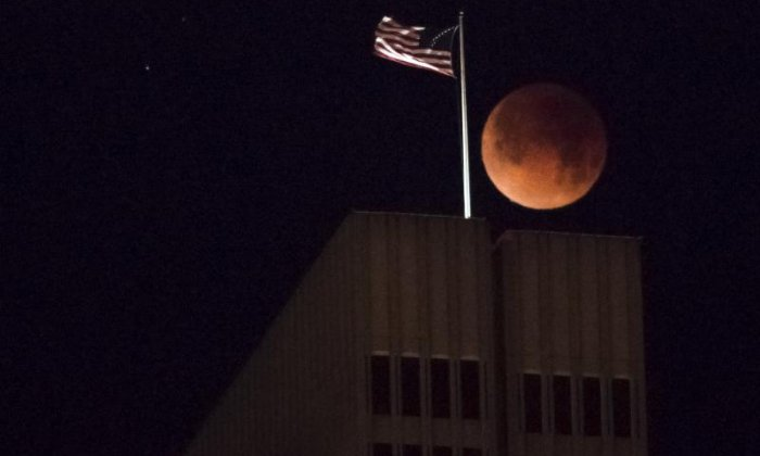 The moon is seen behind a US flag
