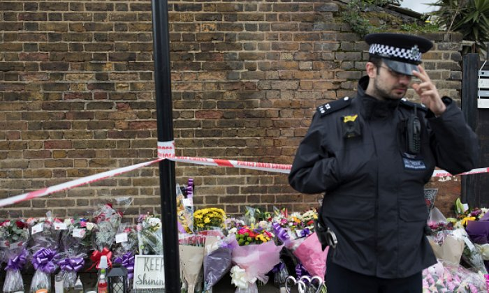 A police officer stands beside floral tributes at the scene where Tanesha Melbourne, 17, was murdered