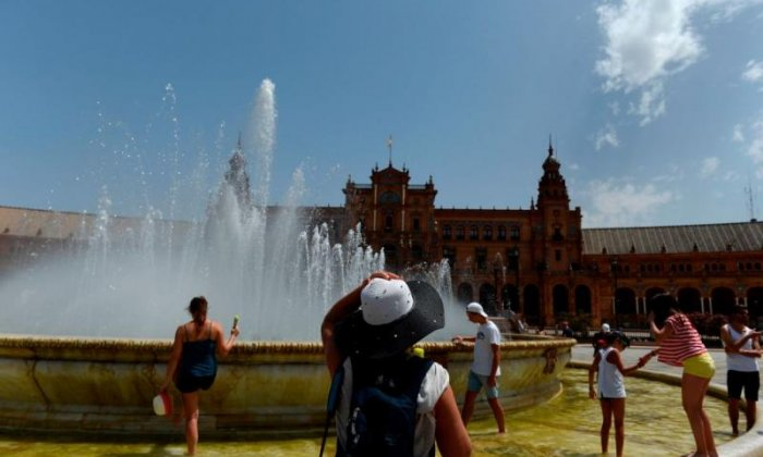 People cool off in a fountain at Plaza de Espana in Seville