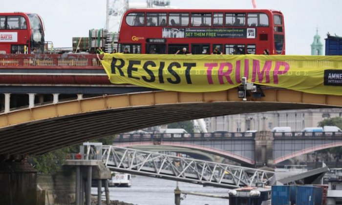 Amnesty International install 'Resist Trump' banners on a bridge in London
