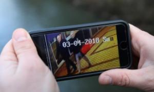A journalist shows CCTV footage of Sergei Skripal and his daughter on a mobile phone. Both were later found unconscious