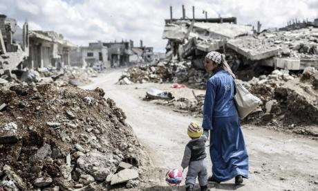 A woman walks past wreckage in Kobani, one of the focal points of the Syrian conflict. Syria has witnessed almost daily violence since conflict broke out in 2011