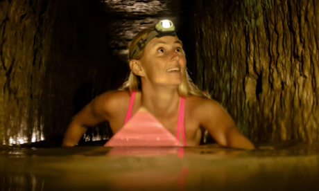Daring American woman travels Paris catacombs in a bikini on a surfboard