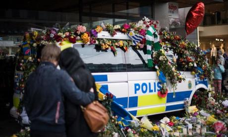 A couple hug in front of a flower covered police car at the site where the truck drove into a department store in Stockholm, Sweden