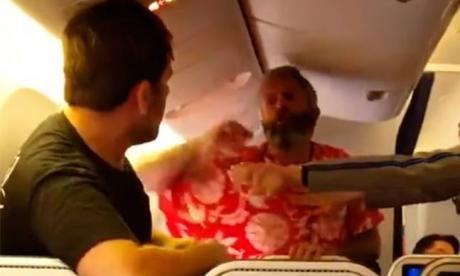 The passenger, in red, can be seen brawling in a video posted on YouTube