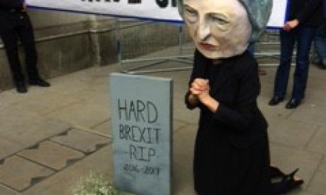 Someone dressed as Theresa May is shown kneeling down