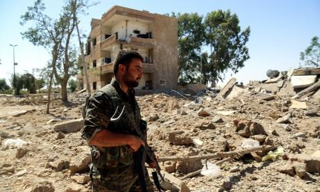 A soldier supporting the SDF is seen patrolling the outskirts of Raqqa on June 27, 2017