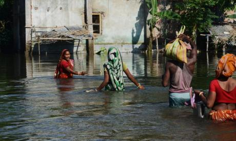 Villagers in India wade through the water