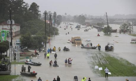 Several people are seen on a flooded street