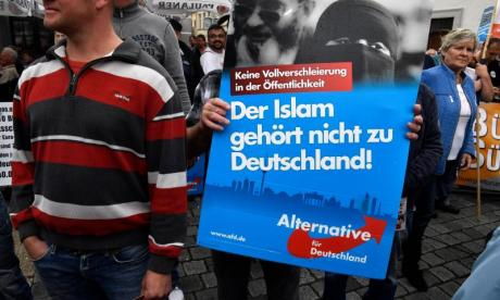 AfD supporters carry slogans against Muslim immigrants during a rally