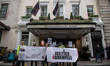 Grenfell Tower campaigns stand in front of the Grand Connaught Rooms as Sir Martin Moore-Bick speaks inside on the opening day of the inquiry into the disaster