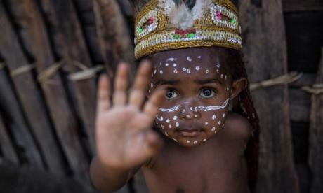 A child looks up at a photographer in West Papua