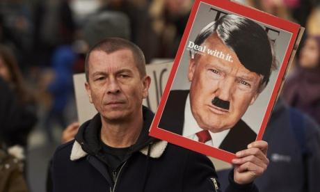 A protestor is seen holding a placard against Donald Trump in February 2017. Further protests are likely following news that the President will visit the UK before the end of the year
